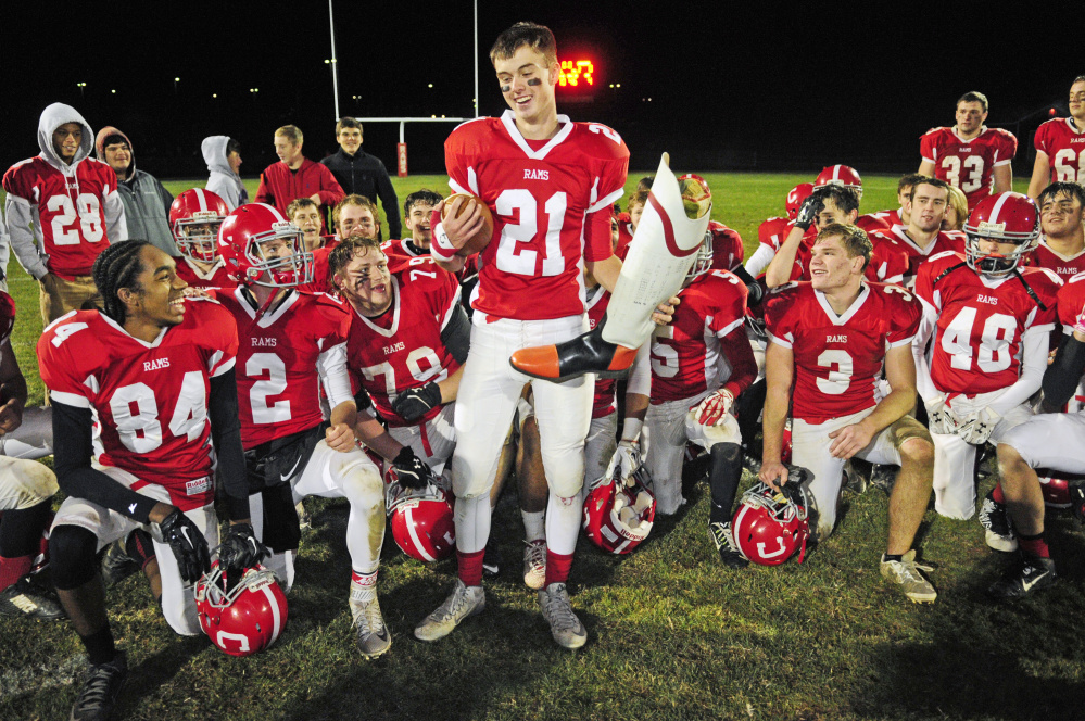 Cony's Lucas Tyler (21) and teammates celebrate with the boot trophy after defeating Gardiner in the 138th game between the long-time rivals Friday at Alumni Field in Augusta.