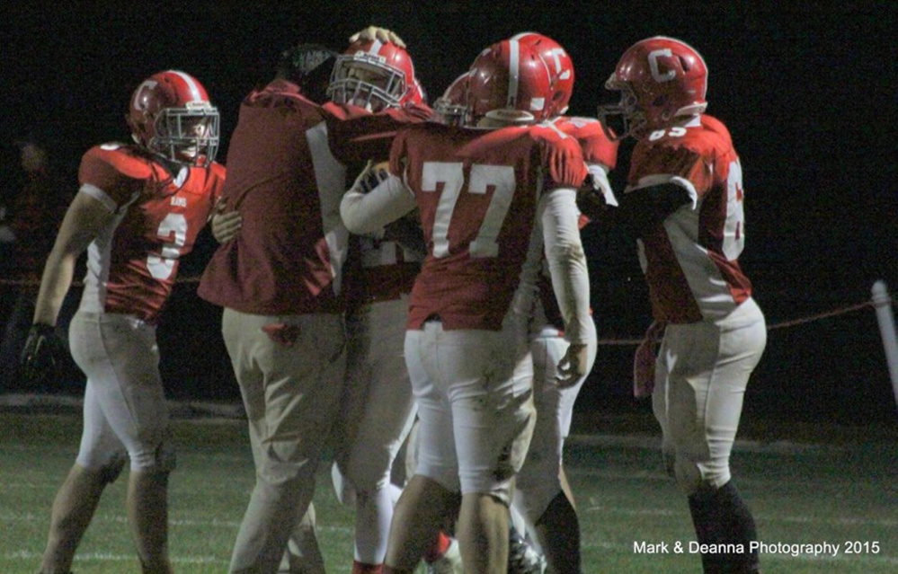 Cony coach B.L. Lippert and the rest of the Rams celebrate with Lucas Tyler after Tyler made an interception against Gardiner on Friday in Augusta.