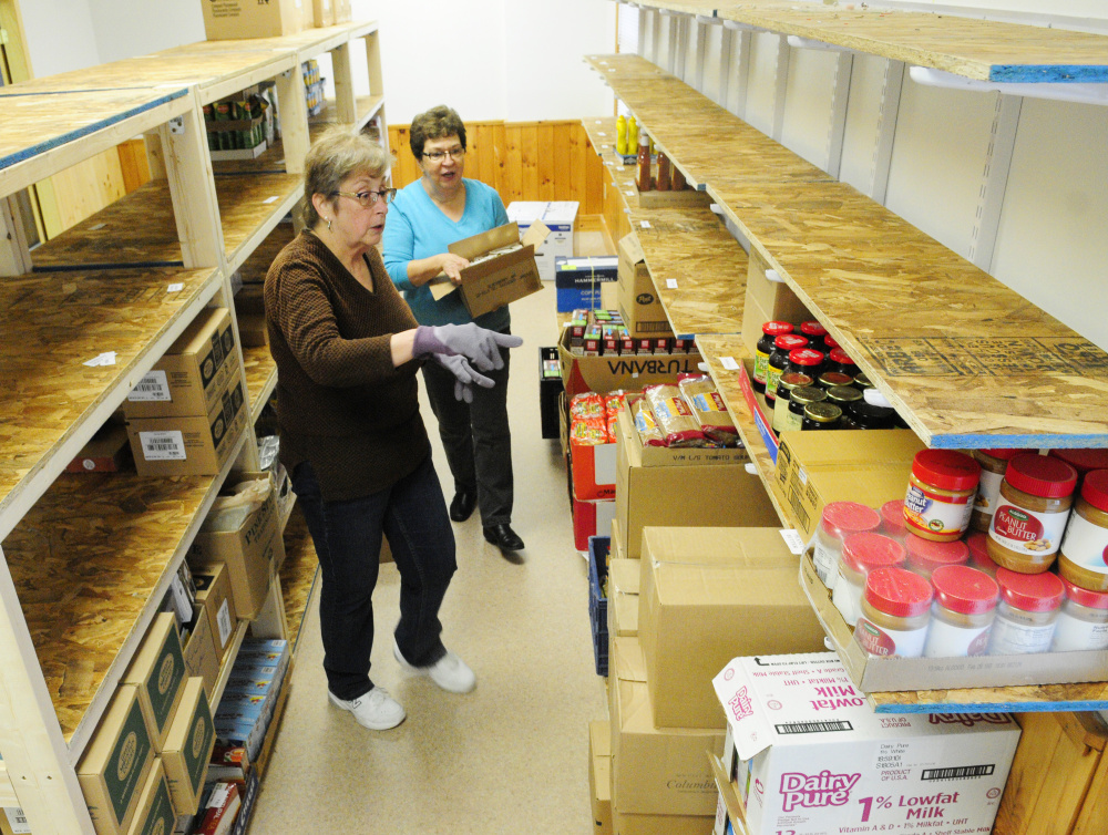Cheryl Cook, left, shows Laverne Pelletier which shelf the jam goes on as they and other volunteers help move the Belgrade-Rome Food Pantry into the North Belgrade Community Center on Thursday.