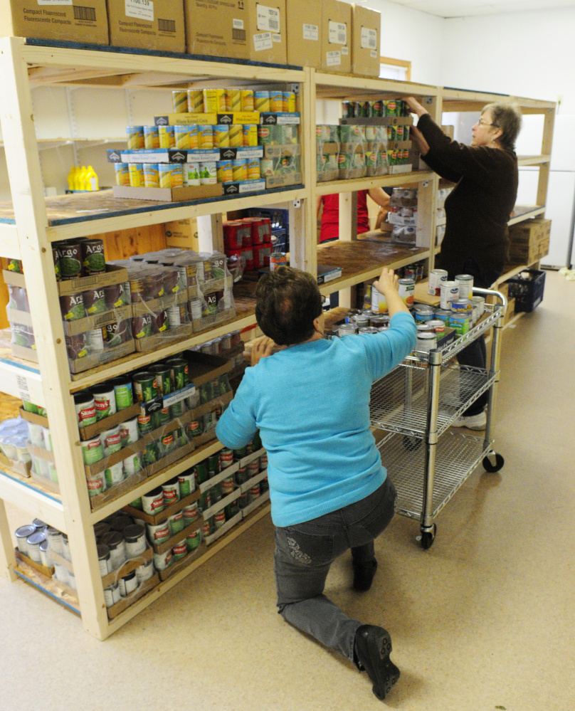 Laverne Pelletier, left, stack cans on shelves as they and other volunteers help move the Belgrade-Rome Food Pantry into the North Belgrade Community Center on Thursday.