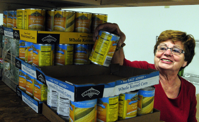 Barbara Smith stacks cans onto shelves as the Belgrade-Rome Food Pantry moves into the North Belgrade Community Center on Thursday.