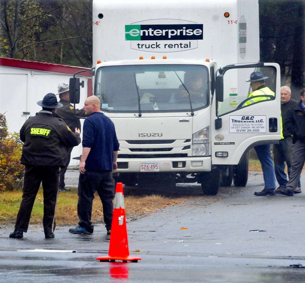 MADISON,ME.-October 29: Police speak with truck driver Harry Cragin, second from left,  following a collision with a vehicle at the intersection of Route 148 and Old County Road in madison on Thursday, October 29, 2015. (Photo by David Leaming/Staff Photographer)