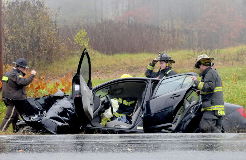 Madison firefighters and police inspect the wreckage of a car at the intersection of Route 148 and Old County Road in Madison that left the female driver with serious injuries on Thursday.