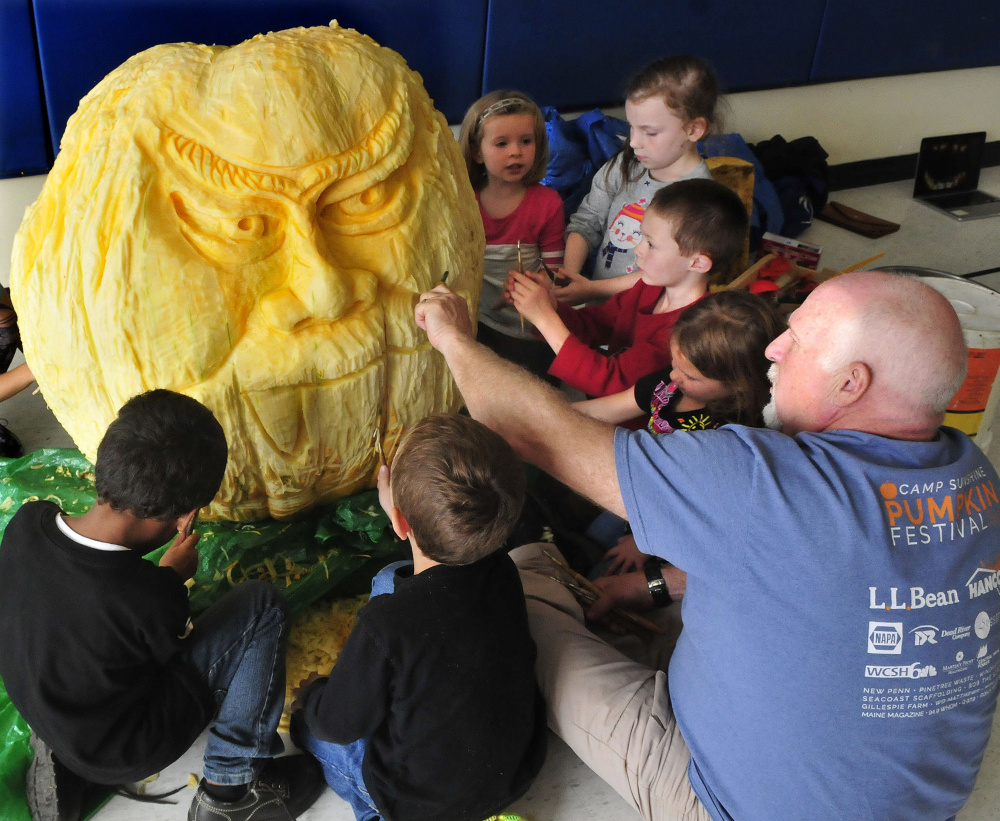 Moe Auger shows kindergarten students how to use tools to carve around the face of a 400-pound pumpkin at North Elementary School in Skowhegan on Thursday.