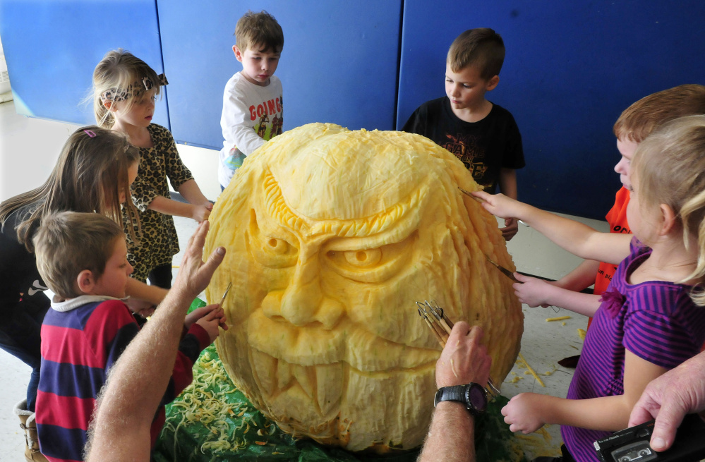 Students at North Elementary School in Skowhegan had their hands full carving a face on a 400-pound pumpkin on Thursday.