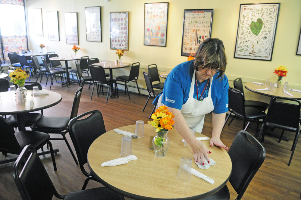 Paula Papsis, one of the volunteers from Molina Healthcare, sets tables before lunch on Friday at Bread of Life Soup Kitchen in Augusta.