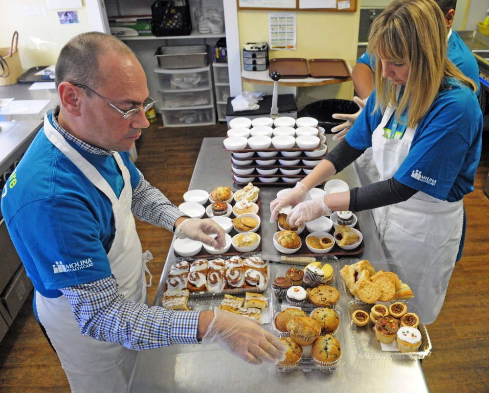 Norman Curtis, left, and Nicole Paul, volunteers from Molina Healthcare, put desserts into serving dishes as they prep for lunch on Friday at Bread of Life Soup Kitchen in Augusta.