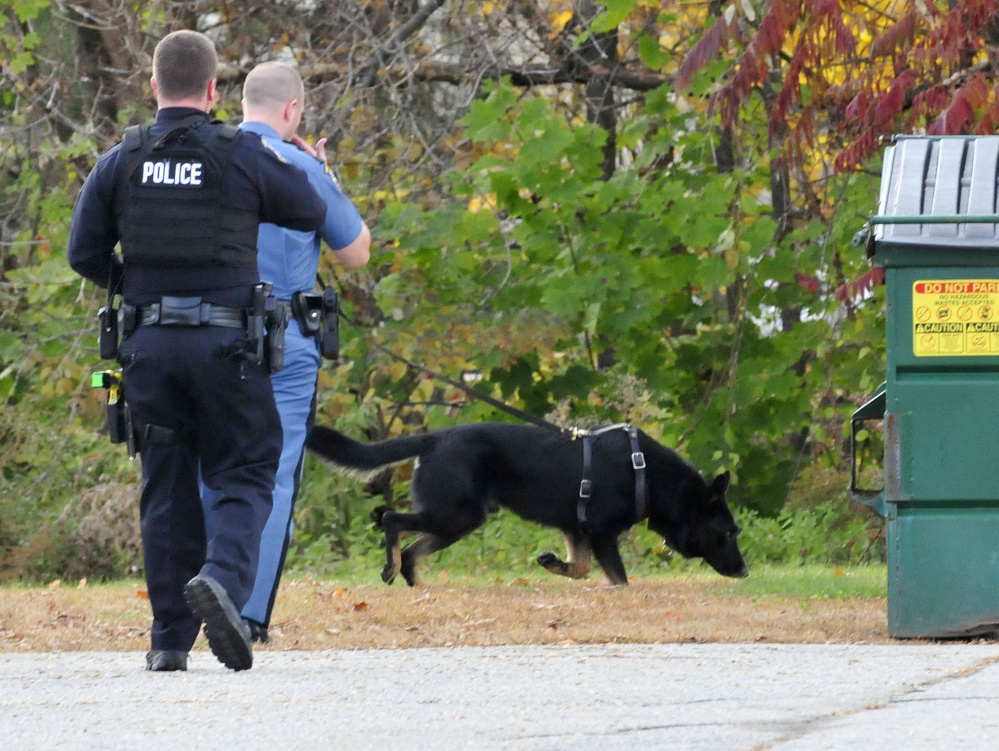 Waterville police officer Cameron Huggins, left, and a state trooper with a tracking dog search for the suspect of a burglary at the Rite Aid store on Main Street in Waterville on Thursday. The suspect, Nathan Boulette, 22, was found dead in a nearby apartment on Friday.