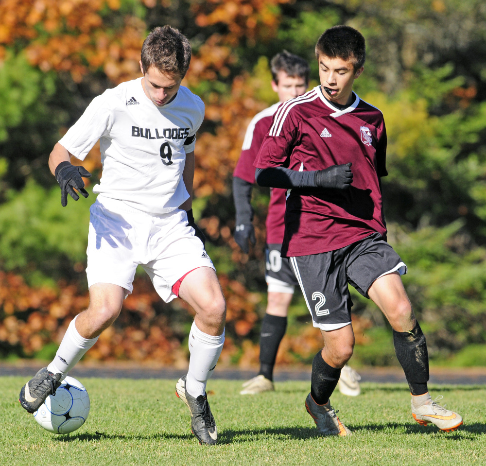 Hall-Dale's Tyler Dubois, left, and Monmouth Academy's Avery Pomerleau battle for the ball during a Class C South semifinal game Wednesday afternoon in Farmingdale. Pomerleau would score in double overtime to give Monmouth a dramatic 2-1 victory.