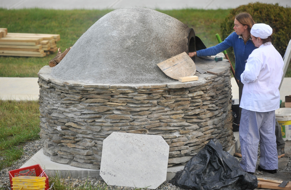 Katherine Creswell, farm manager at Kennebec Valley Community College helps culinary student, Brenda Madden with the wood oven during class at the Alfond campus on Friday.