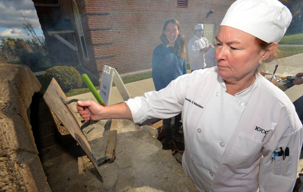 Brenda Madden with the culinary class at Kennebec Valley Community College, checks on her calzone in the wood oven for class at the Alfond campus on Friday.