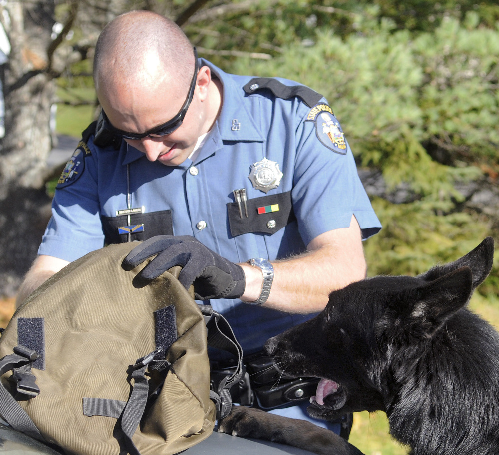 Maine State Police Trooper Chris Rogers searches a satchel as a drug sniffing dog checks out the bag during a traffic stop Friday in Chelsea. Maine State Police, state fire marshal investigators and agents from the Maine Drug Enforcement Agency pulled over the car just before 1 p.m. on Hallowell Road and removed the driver and passengers at gun point.