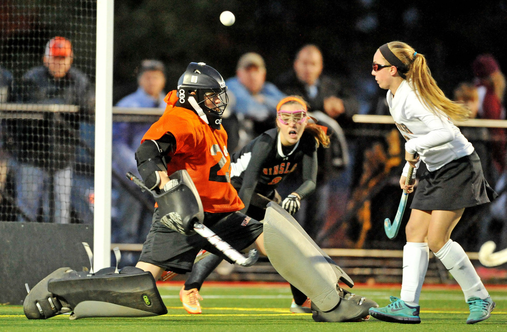 Winslow goalie Delaney Wood watches a shot off the stick of Gardiner's Amanda Cameron, right, head toward the cage as Winslow's Susan Grant (8) defends during the Class B North final.