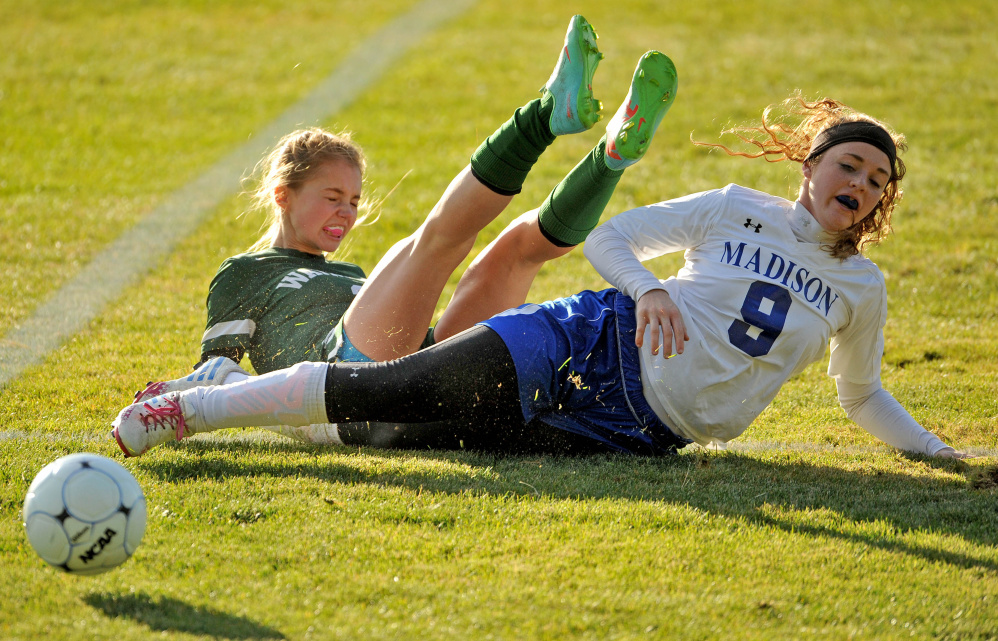 Madison's Marah Hall (9) slide tackles Waynflete's Ava Farrar (2) during a Class C South semifinal game Friday in Madison.