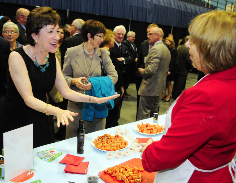 U.S. Sen. Susan Collins, left, talks with Backyard Farms employee Beth Driggs about the tomatoes grown in Madison that were available for sampling before the Maine State Chamber of Commerce dinner on Friday at the Augusta Civic Center.