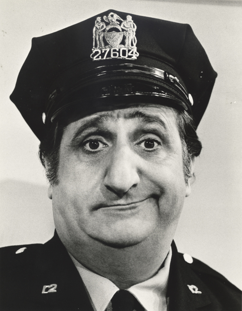 """In a photo, provided in 1974 by ABC, actor Al Molinaro poses dressed as Murray the cop. Molinaro, the loveable character actor with the hangdog face who was known to millions of TV viewers for playing Murray on """"The Odd Couple"""" and malt shop owner Al Delvecchio on """"Happy Days,"""" died Friday."""