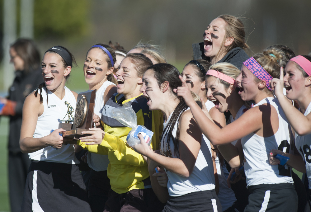 Members of the Skowhegan field hockey team celebrate their 3-1 victory over Thorton Academy in the Class A state championship game Saturday in Orono.