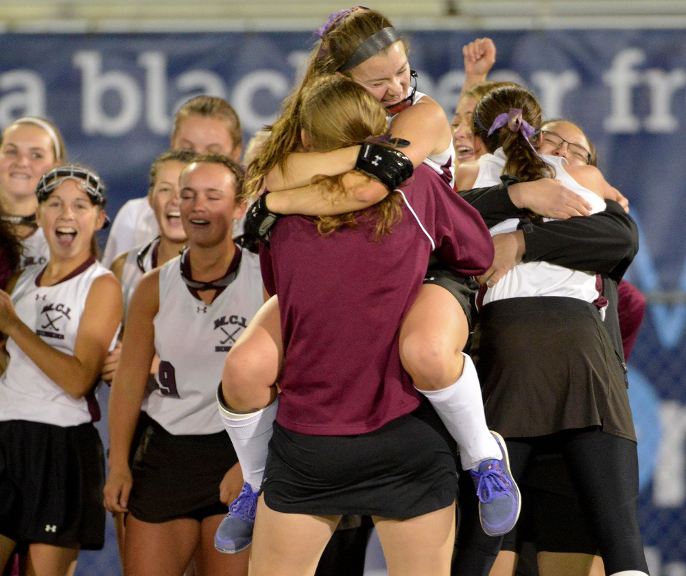 Maine Central Institute's Allison Hughes, facing, jumps into the arms of a teammate after defeating Oak Hill High School 3-0 for the Class C state championship game Saturday at Morse Field at the University of Maine in Orono.