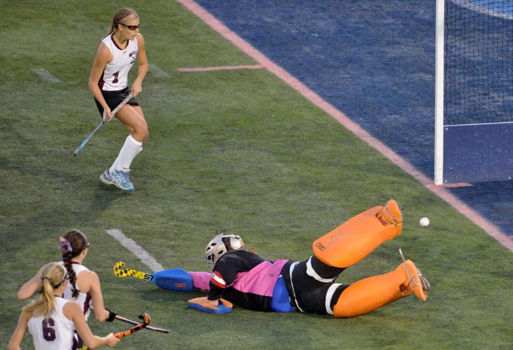 Oak Hill High School goalie Abby Fuller (00) dives for the save on a shot by Maine Central Institute's Addie Williams (4) as teammate Madisyn Hartley (1) watches for the rebound during the Class C state championship game Saturday at Morse Field at the University of Maine in Orono.