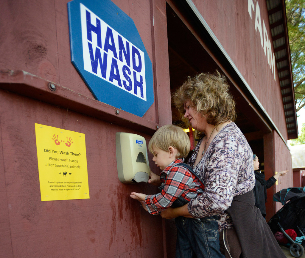 Two-year-old Tripp Proctor gets help from his grandmother Joann Harmon both of Bridgeton as they wash their hands after visiting Old McDonald's Farm petting zoo at the Fryeburg Fair.