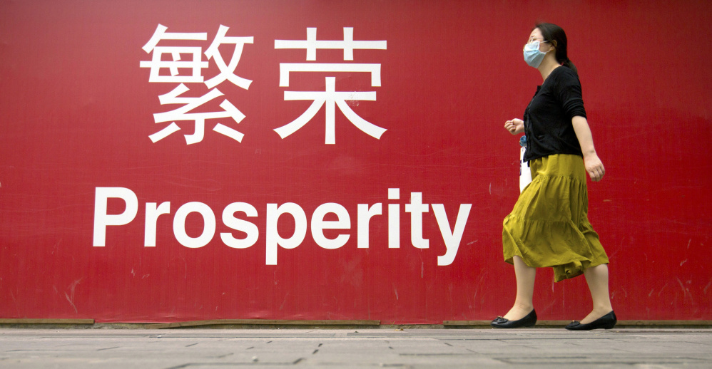 A woman walks past a banner in Beijing. Fears about China's slowdown and a future U.S. interest rate hike have sent global stock markets into a fidgety freefall.