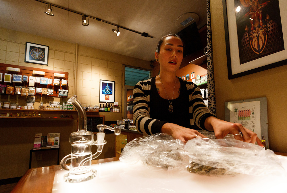Esther Aldrich looks through bags of cannabis buds at Amazon Organics, a pot dispensary in Eugene, Ore., on Monday as she prepares for legalization.