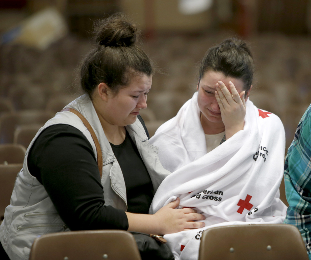 Hannah Miles, right, sits with her sister Hailey after Hannah was reunited with her family in Roseburg, Oregon, on Thursday after a deadly shooting at Umpqua Community College.