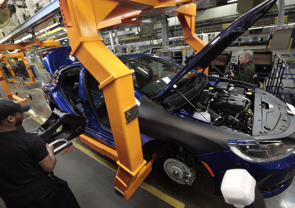 An assembly line worker builds a 2015 Chrysler 200 at the plant in Sterling Heights, Mich. Fiat Chrysler's U.S. sales jumped nearly 14 percent in September, helped by the automaker's Jeep brand. Fiat Chrysler's factory workers rejected a proposed contract Thursday, however.
