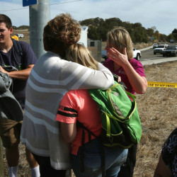 Bystanders console each other on a road leading to the Umpqua Community College campus in Roseburg, Ore. Thursday, Oct. 1, 2015, following a deadly shooting at the school.