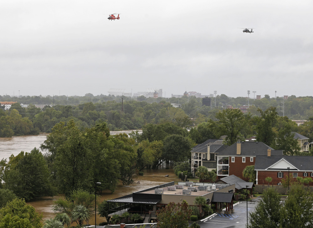 Helicopters fly over the Congaree River, swollen with floodwaters, near the Gervais Street bridge in West Columbia, S.C., Sunday, Oct. 4, 2015. Hundreds were rescued from fast-moving floodwaters Sunday in South Carolina as days of driving rain hit a dangerous crescendo that buckled buildings and roads, closed a major East Coast interstate route and threatened the drinking water supply for the capital city.