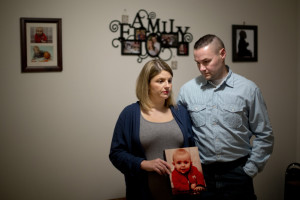 Jon and Beth Guay hold a photo of their son, Colton, on Wednesday at their home in Poland. Colton died Monday of complications from a disease caused by E. coli bacteria, which his family thinks he contracted by touching animals at the Oxford County Fair's petting zoo last month.