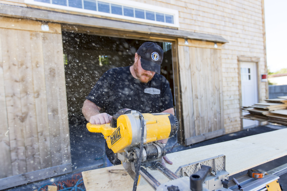 Alex Anastasoff, of the forthcoming Fore River Brewery, cuts lumber while renovating the company's headquarters.