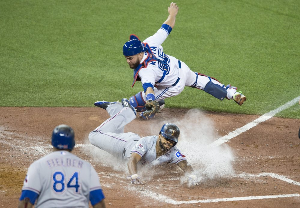 Texas' Delino DeShields gets past Blue Jays catcher Russell Martin to score in the third inning.