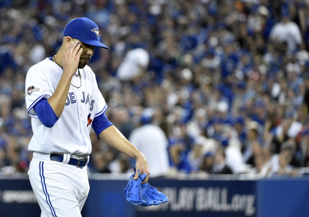 Blue Jays starting pitcher David Price walks back to the dugout in seventh inning. Price gave up all five Texas runs and took the loss.