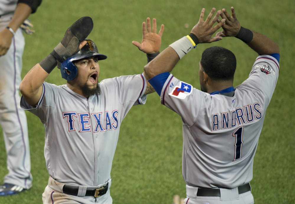 The Rangers' Rougned Odor, left, and Elvis Andrus celebrate after Odor scored to break a 4-4 tie in the 14th inning of Friday's American League Division Series game. The Rangers took a 2-0 lead in the best-of-five series.