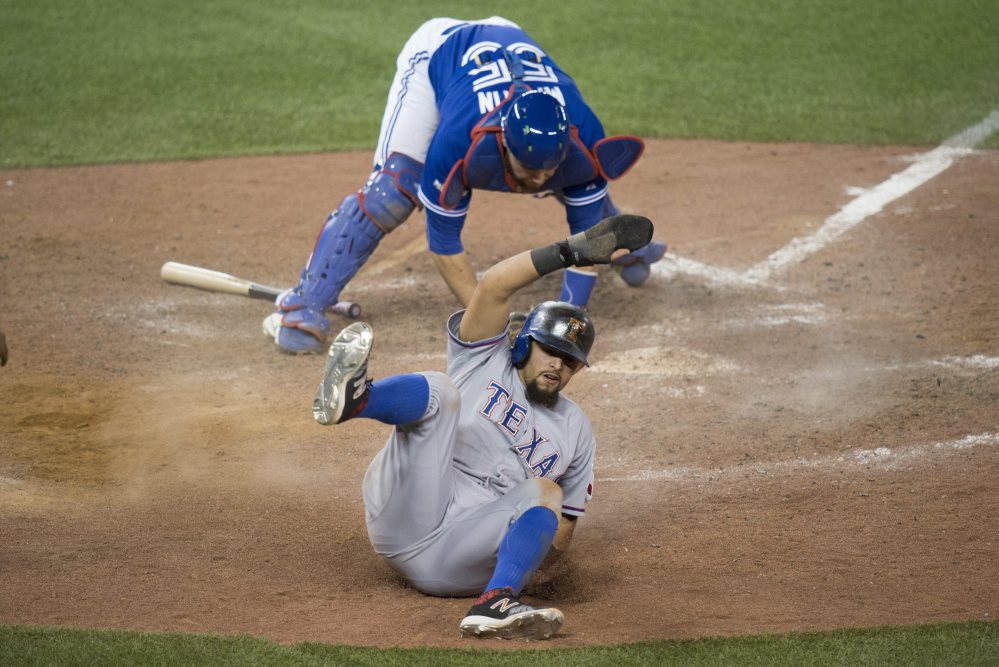 Odor slides safely past the tag of Blue Jays catcher Russell Martin to score in the 14th inning.