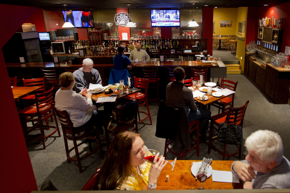 Customers enjoy dinner and drinks at Stirling & Mull in Freeport as hockey on television and pop tunes on the radio fill the air Wednesday.