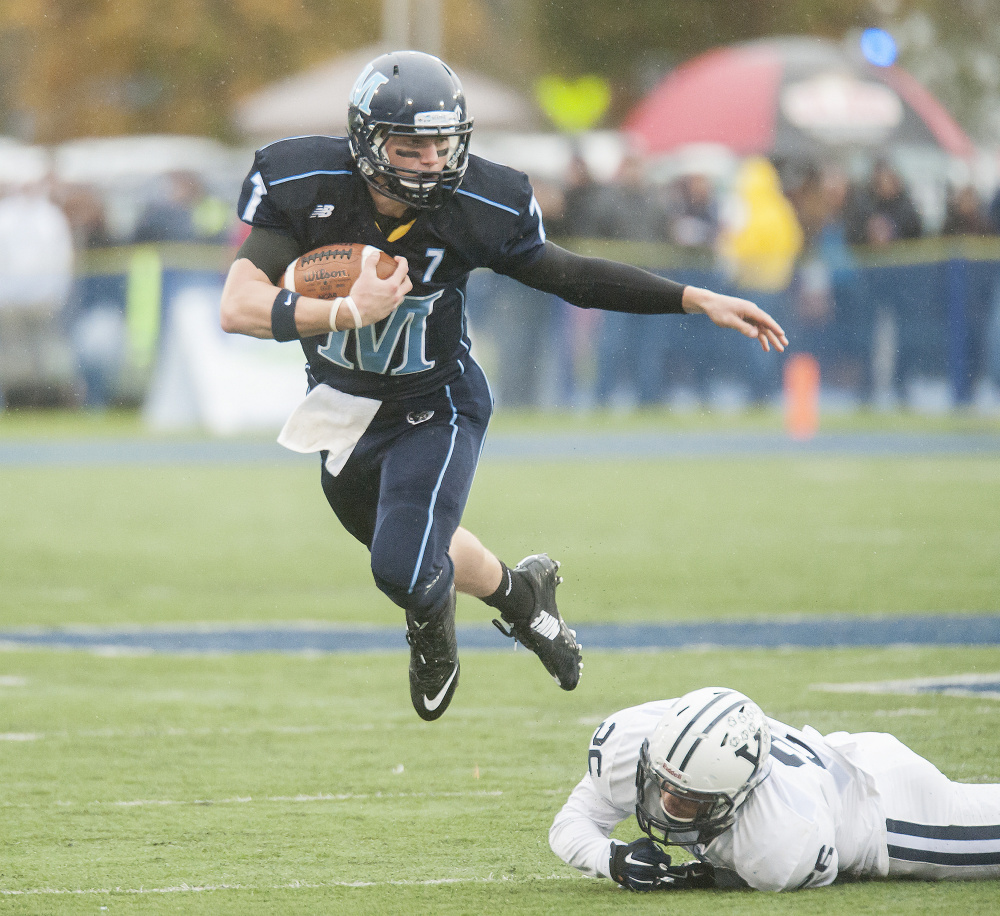 Maine quarterback Dan Collins escapes from Hayden Carlson of Yale in the first half. Collins was 19 of 49 for 199 yards.