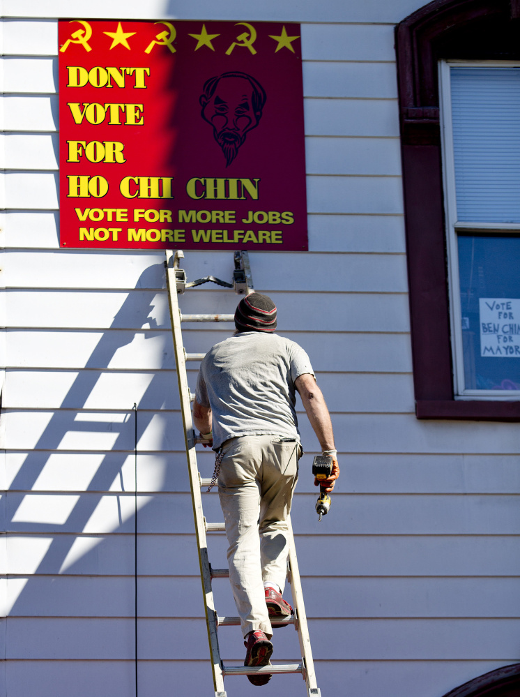 A worker for the owner of 109 Pine St. in Lewiston prepares Monday to remove a political sign containing communist symbols and a racial message. The sign refers to mayoral candidate Ben Chin, a third-generation American whose grandparents emigrated from China to the U.S.