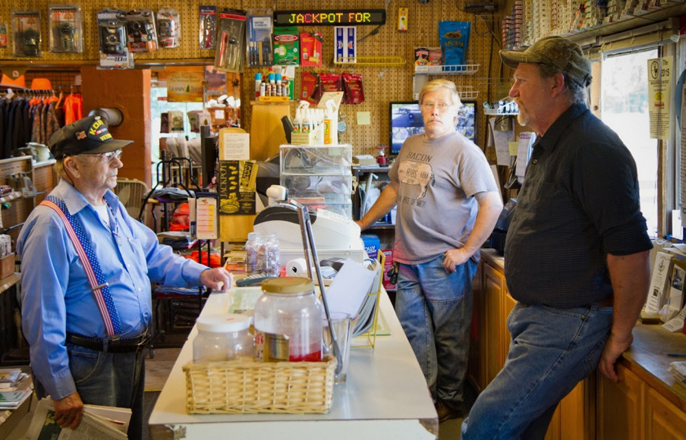 Shop co-owners Wayne Seidl, front right, and Joe Ruff, back right, talk with a customer at the Waite General Store. Residents of the small Washington County town of Waite, population 101, purchase more lottery tickets per capita than any other town in the state, according to lottery sales data.