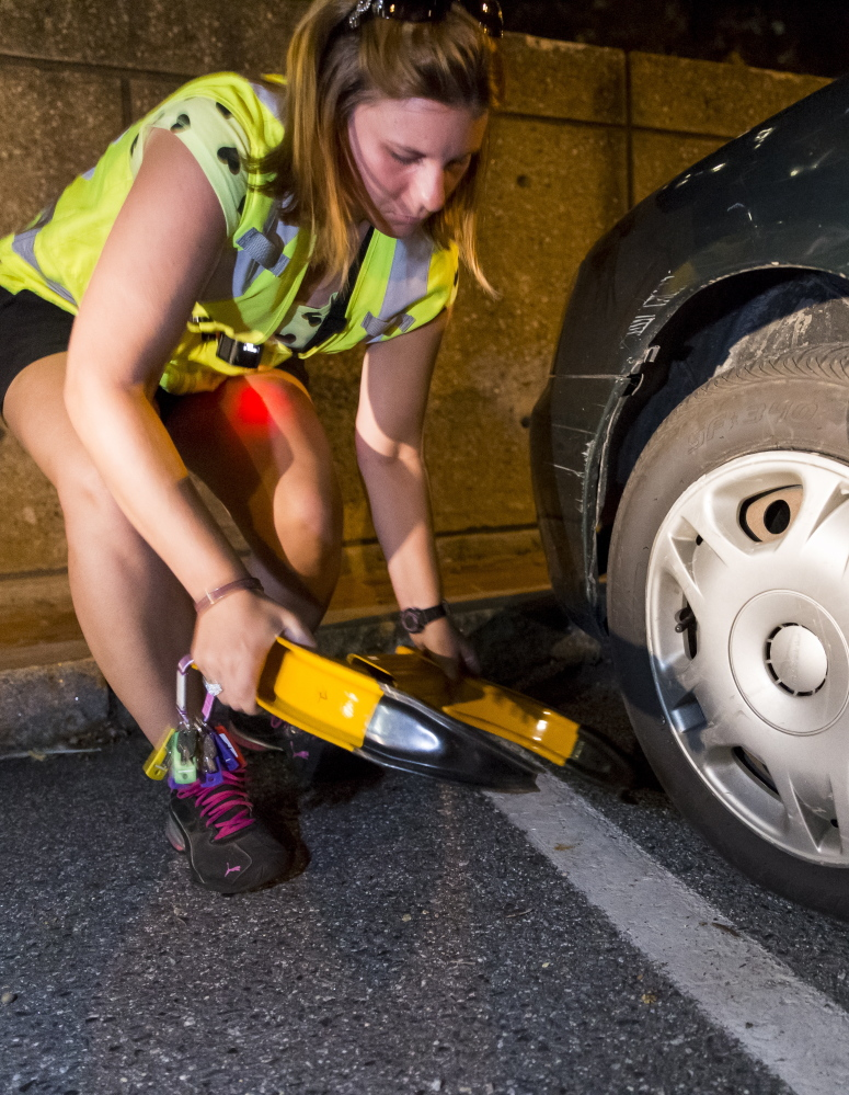 Shannon Farrell removes a boot from a car in Portland. City records show she was one of two parking lot workers identified in an investigation involving Rachel Talbot Ross.