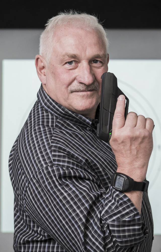 Gun designer Ernst Mauch poses with the Armatix iP1 he designed. He is in the U.S. this week, looking into starting a new company to make smart guns that police can use.