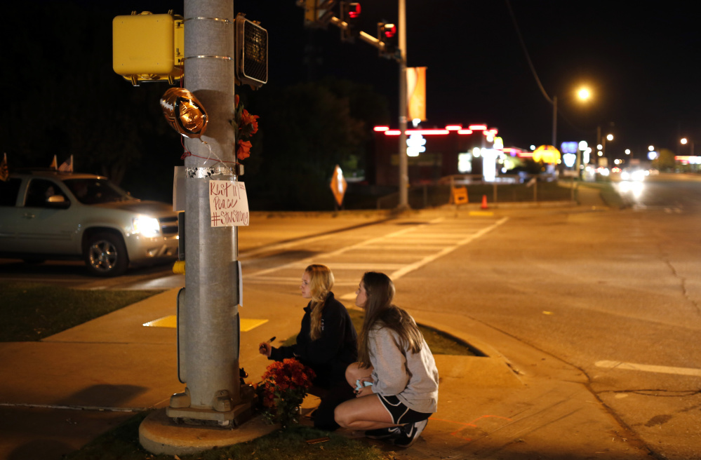 Oklahoma State students Kelly Cooke, left, and Rebecca Buchanan read messages on a memorial in Stillwater, Okla., on Saturday, near where a car crashed into spectators at the homecoming parade, killing four people.