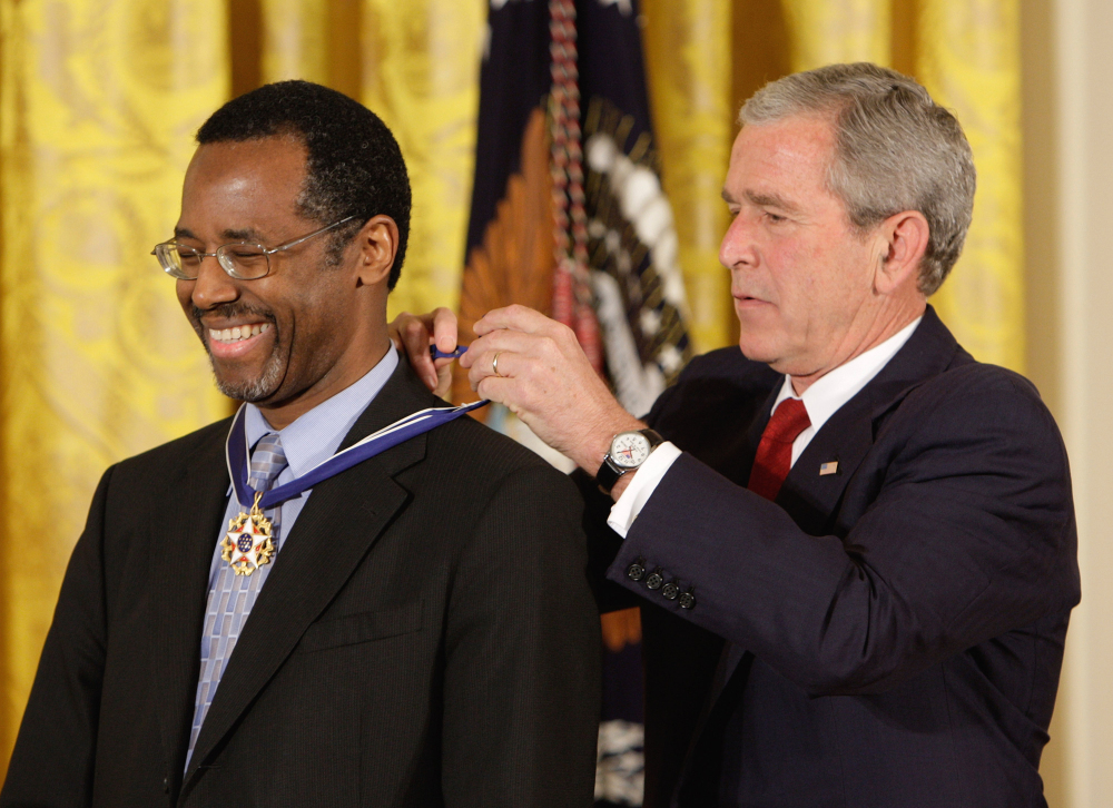 In this June 19, 2008, file photo, President George W. Bush places the Presidential Medal of Freedom on Johns Hopkins University's then-director of pediatric neurosurgery Dr. Ben Carson, as he takes part in a ceremony for the 2008 recipients of the Presidential Medal of Freedom, in the  East Room at the White House in Washington.