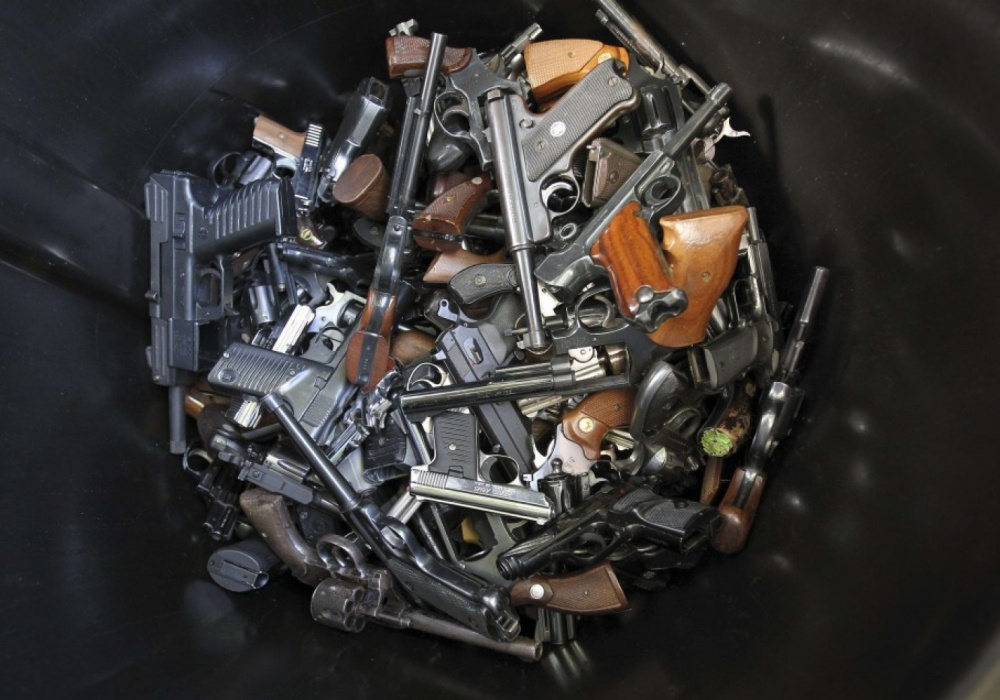 Handguns that were turned in by their owners are collected in a trash bin at a gun buyback program in Los Angeles following the mass shooting at Sandy Hook Elementary School in Connecticut in 2012.