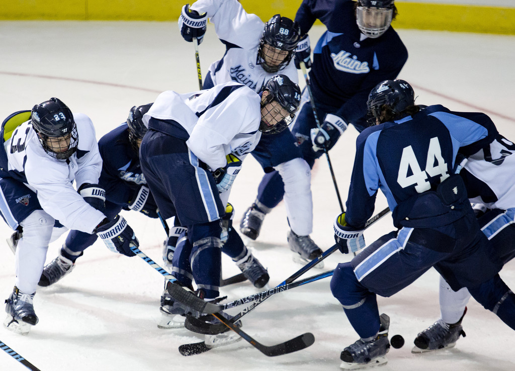 A scramble for the puck ensues at Maine's practice, led by Sam Becker, left; Cedric Lacroix, center; Brian Morgan, center rear; and Conor Riley, right. The Black Bears are coming off three straight losing seasons. Gabe Souza/Staff Photographer
