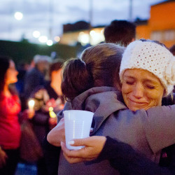 """Jessica Elwell, right, hugs her friend Morgan McKee after Monday's candlelight vigil at the Fishermen's Memorial in Rockland. The women went to high school with Dylan Meklin, a crew member on the El Far. """"He was always such a humble kid,"""" said Elwell."""
