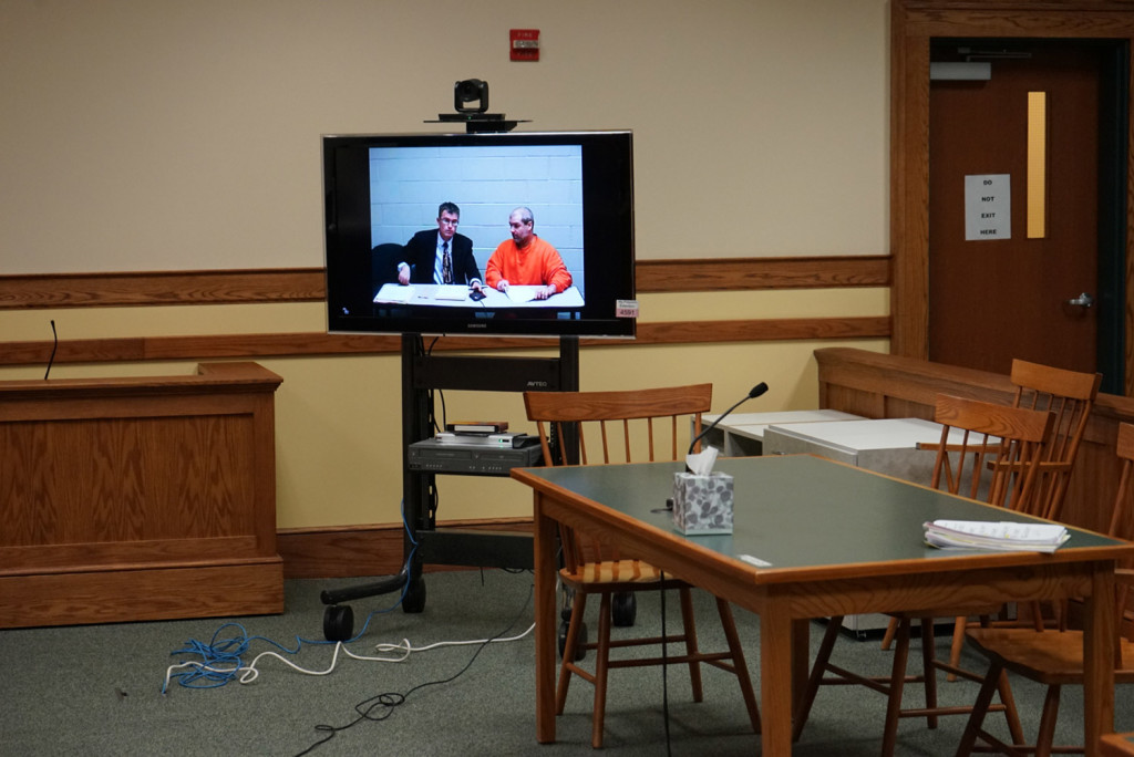 Christopher Hall, right, appears via video link from jail in Springvale District Court with defense attorney Randall Bates for Hall's initial appearance on assault charges in connection with an attack on a lawyer using a cane equipped with a shocking device.