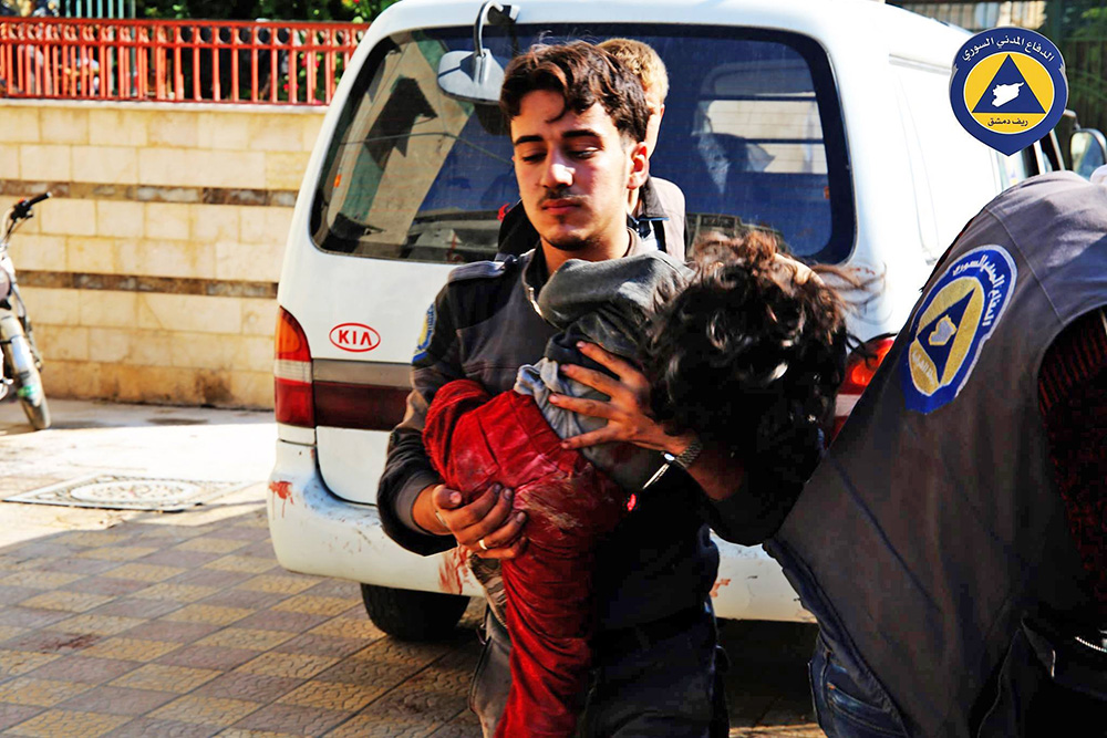 A paramedic holds a child who witnesses said was hit by Syrian government missiles Friday. The Syrian Observatory for Human Rights and the Local Coordination Committees group said government forces fired more than 11 missiles at the market, killing at least 40 people. Syrian Civil Defence via AP