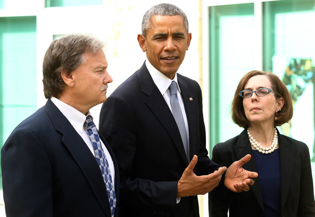 """Roseburg Mayor Larry Rich, left, and Oregon Gov. Kate Brown look on Friday as President Obama makes a statement at Roseburg High School after speaking with families of victims of the Umpqua Community College shooting. He said, """"We're going to have to come together as a country to see how we can prevent these issues from taking place."""" Michael Sullivan/The News-Review via AP"""